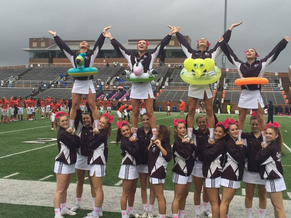 Varsity Cheerleaders encourage the fans on a soggy day Saturday at Rhodes Stadium. The