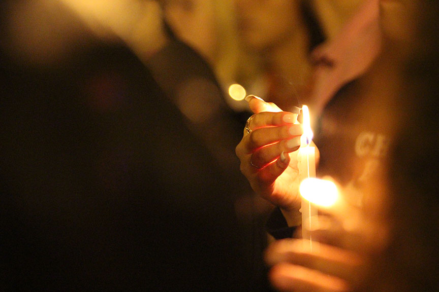 A Cinco Ranch student protects her candle from wind on the evening of Sunday, Dec. 7 at a vigil held for sophomore Terra Kubala.