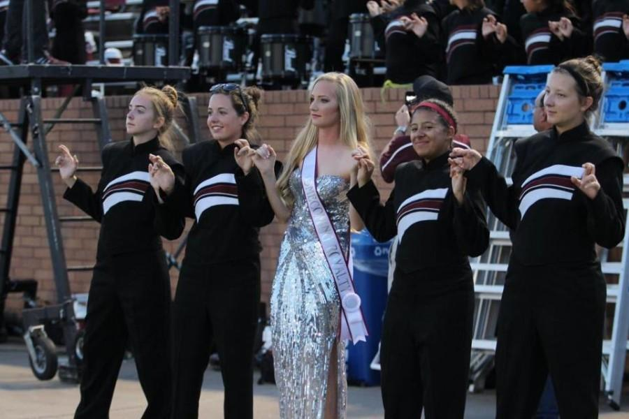 From left to right: Julia Culp, Daniela Ichter, Abby Draut, Susanna Simmonds, and Kyran Hogan all link pinkies and cross their fingers as the band plays the alma mater.