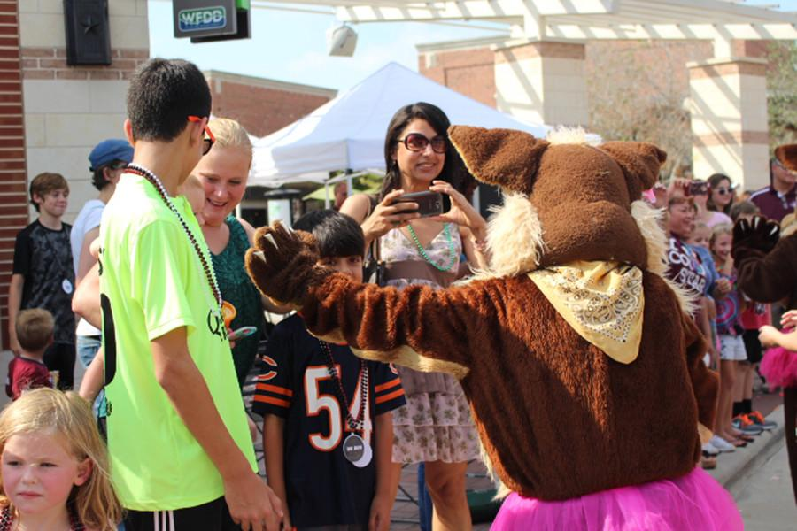 The+CRJH+mascot+reaches+out+to+give+a+toddler+a+high+five.+The+CRJH+cheerleaders+participated+in+Monday%27s+parade+and+shared+some+Coyote+spirit.