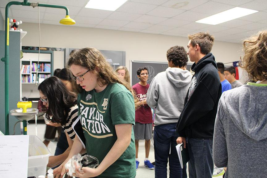 Safety+first%21+Students+line+up+and+prepare+their+goggles+to+wear+before+heading+over+to+their+lab+stations.+