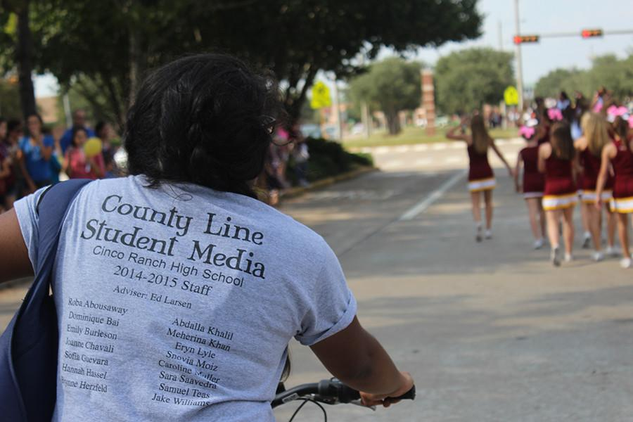 County Line News Editor, junior Joanne Chavali, heads out on her bike to distribute teasers of the cover of the news-magazine and candy goodies to the crowd, hoping to spread the word about their work.