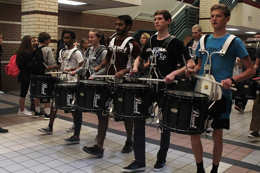 Band members are a part of the procession. These snare players march through the hallway.