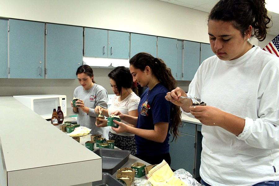 Juniors Julia Douglas, Venae Gonzalez, Bianca Chavez, and Angela Franco begin the decorating process of their cupcakes.