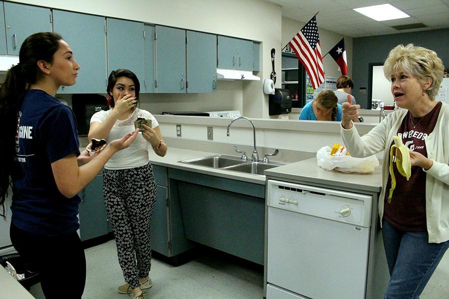 Juniors Bianca Chavez and Venae Gonzalez speak to their teacher, Melinda Kowalczuk, after decorating and tasting their cupcakes.