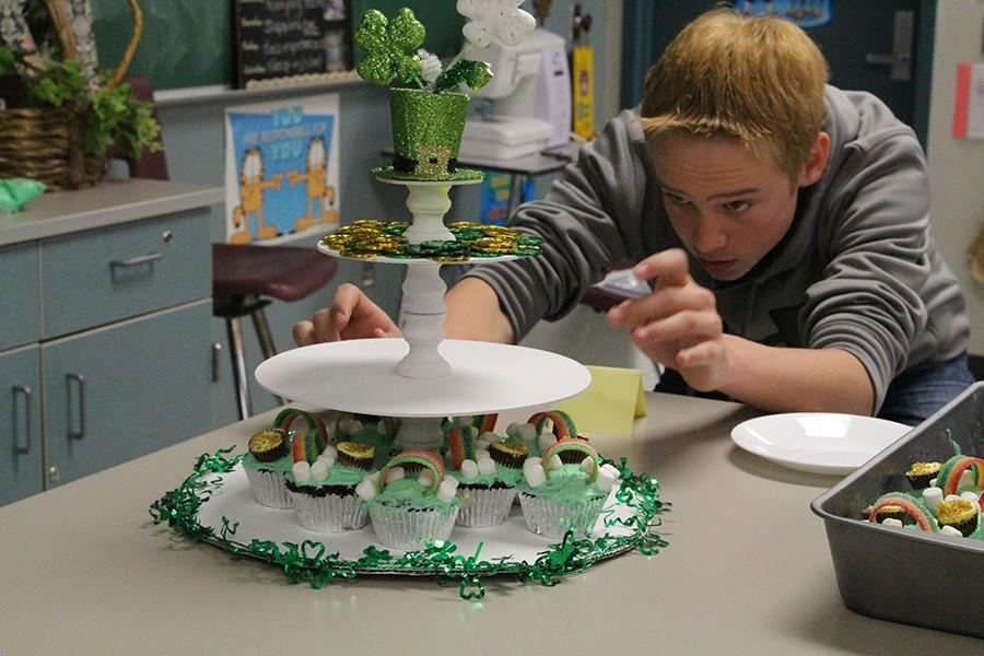 Freshman Blake Alcede carefully places his cupcakes as presentation is very important in the judging process.