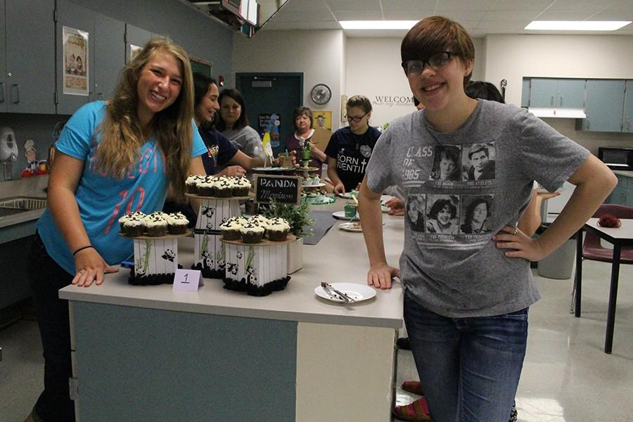 Sophomore Abby Comin and Senior Bonnie Holt and her teammate stand with their winning cupcake presentation.