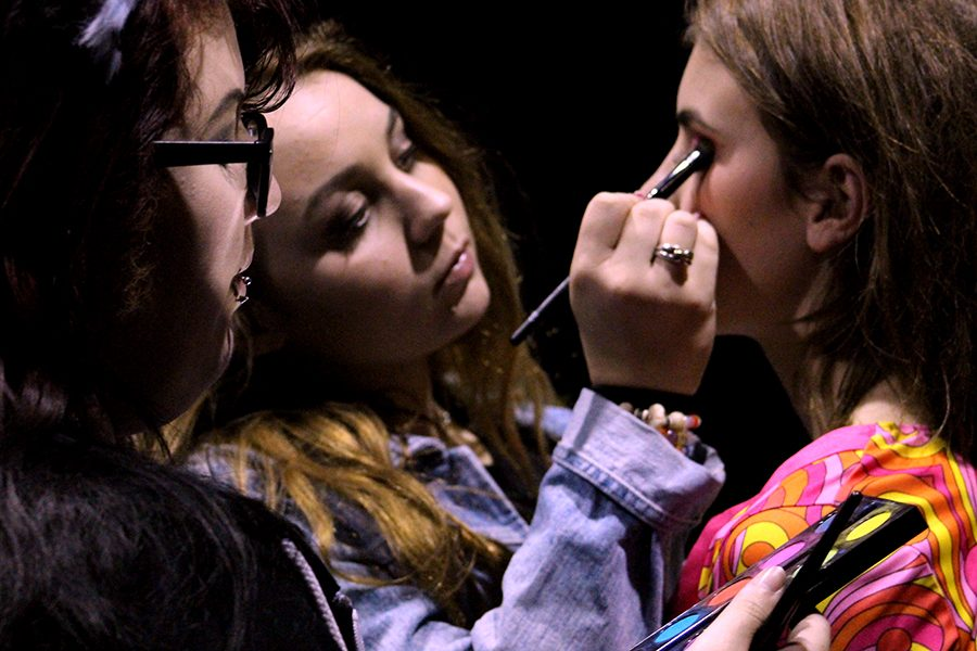Junior Anna Claire Galli and senior Cecily Lazaro apply makeup to Elyssabeth Pratt who played thhe mayor and one of the Venus-A-Go-Go dancers between acts.