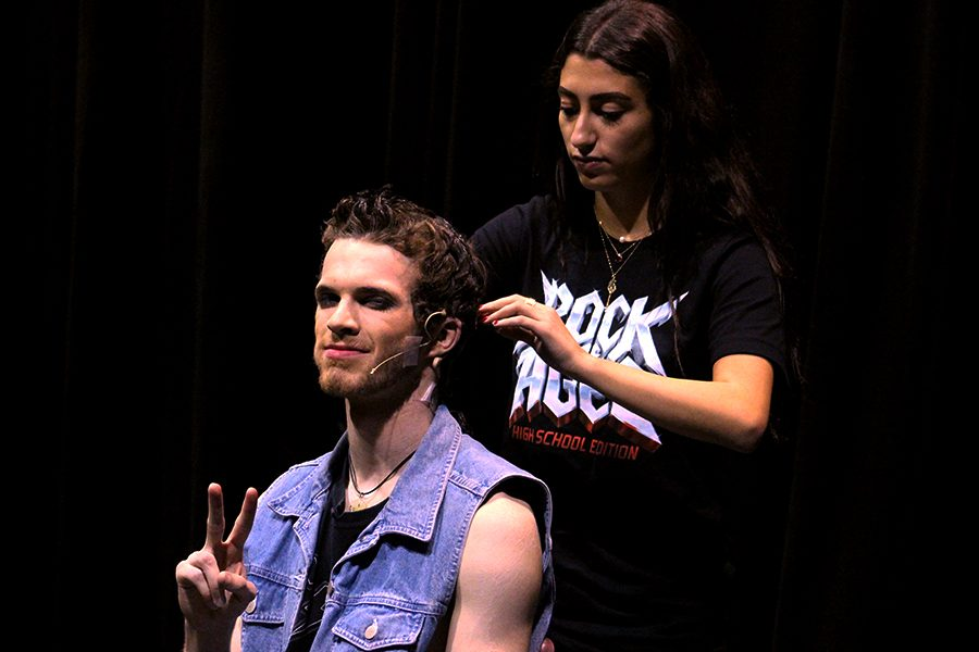 Senior Joya Atallah begins to fix Boyd's hair during intermission. His hair style changes from Act 1 to Act 2, so dress rehearsals like this one allow hair stylists to practice getting an actor ready for the stage.
