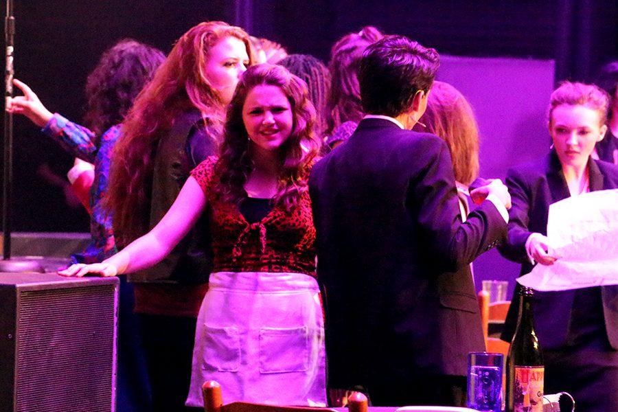 Waitress #1, played by senior Hannah Fallin, protests as Franz Klinemann, played by senior Diego Villanueva, begins to take measurements of The Bourban room while Stacee Jaxx (Stewart) performs for the crowd. The bar was forcefully seized from Dennis Dupree (Regner) by the Klinemann's push for clean living.