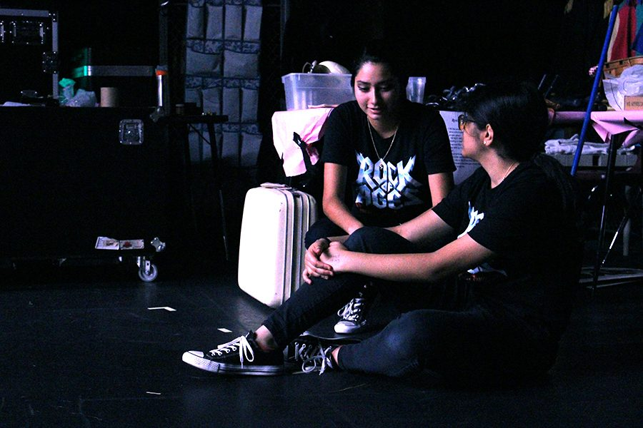 Crew members Anna Medina and Arya Bhakare rest for a few moments in between scene changes. They are a part of the team that moves the set, adjusts lighting and sound, and lowers and raises the curtain.