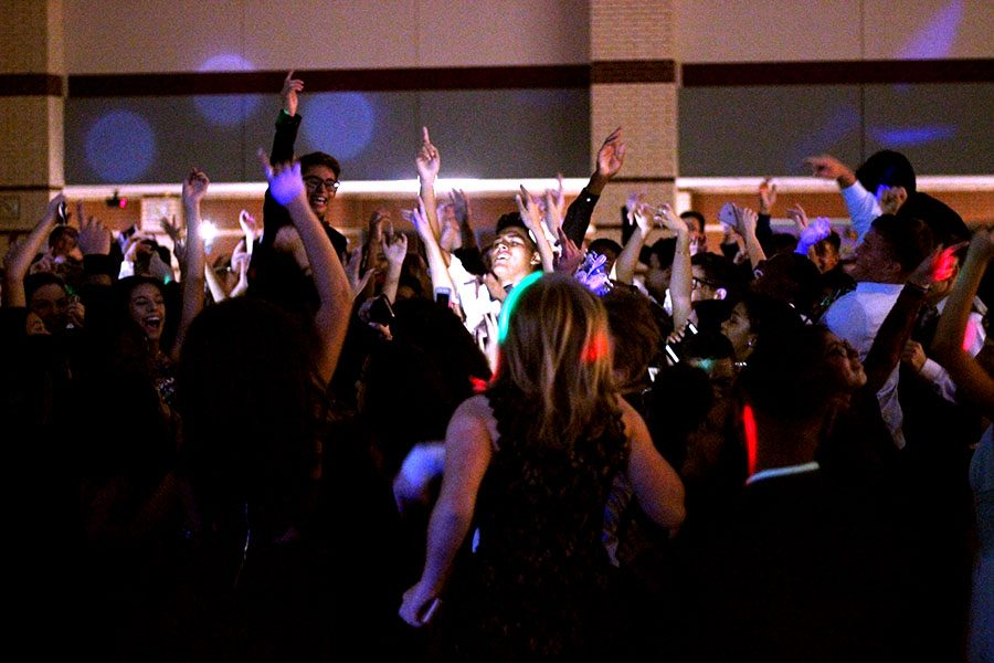 Students dance together as music rings out from the DJ. Student Council also cleans up after the dance. They pop all the balloons and clean up the paper decorations after the dance is over.