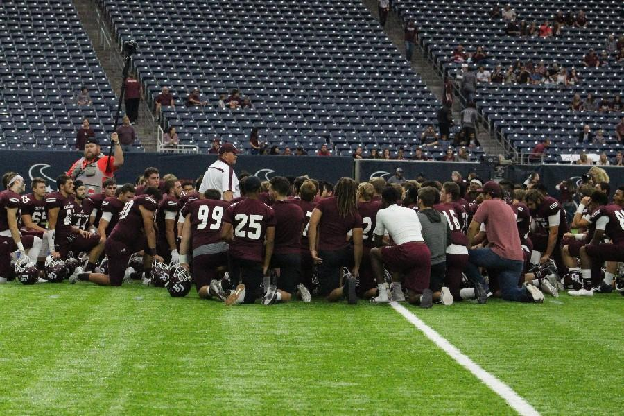 Players+kneel+around+Head+Coach+Don+Clayton+at+the+beginning+of+round+three%27s+game+against+Friendswood.+