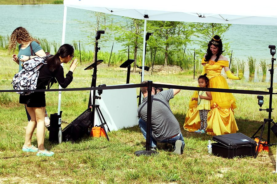Princess Belle, protagonist of recent live-action movie, Beauty and the Beast, stands with a child as her mom and a professional photographer takes pictures.