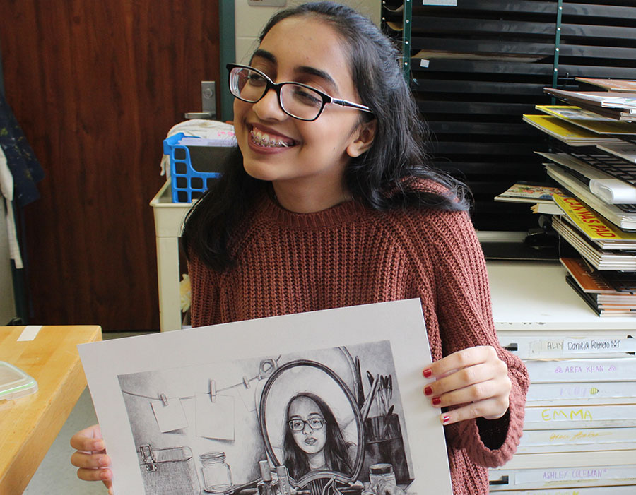 Khan holds one of her pieces  in front of her. Applying to an art college requires not only creating art, but also writing about it.