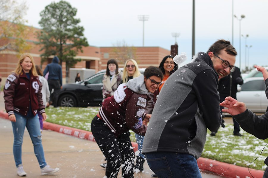 Senior Diego Velaochega pummels his classmate, senior Luke Schaefer, with a snowball. Several students initiated snowball fights before school and during 2.5.
