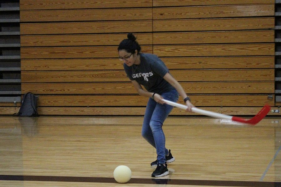 Senior Ana Medina, a member of team Greenland, sets up a shot during a game of hockey in the gym.