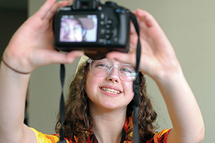 Student snaps a photo of herself with her camera.