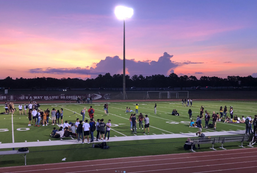 The class of 2020 relaxes on the field watching the sun slowly rise.