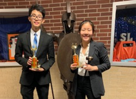 Sophomore Henry Ding and Anabelle Du pose with their public forum trophies.