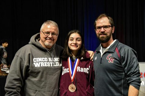 Coaches Bill Dushane and Luke McConn stand with junior Isabella Walsh after she receives her fourth place medal.