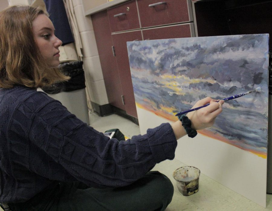 A National Art Honor Society student works on a painting of a sunset.