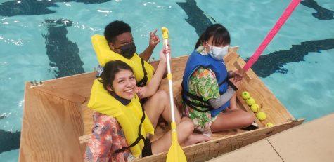 Ashlynn Deadrick (Top), Valerie Bedoya Moncada (Left), and Jamie Kelly (Right), row their boats across the pool. Kelly holds a sword in her hands.